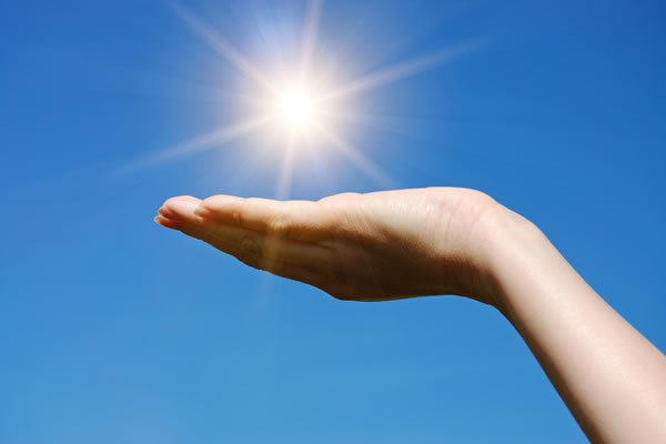 female hand appears to hold up the sun